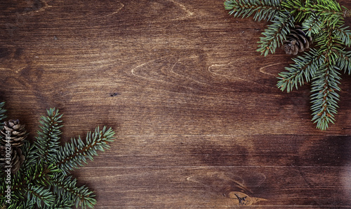 Fototapeta New Year's background. Spruce branches on a wooden table. Ornaments for the New Year tree. Christmas concept. obraz