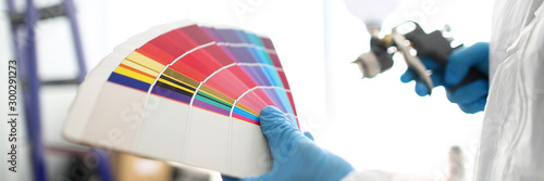 Hands of workman holding airbrush and colorful fantail picking wall tone to pain Canvas Print