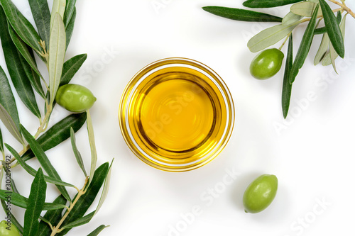 Fototapeta Olive oil. Greek olive oil in glass transparent bowl with branches with leaves and olives, with copy space. Close-up, on white background. obraz