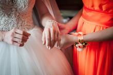 Bridesmaid In Orange Dress Helps Bride To Wear Bracelet