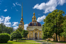 Russia, Saint Petersburg, Near Neva River Peter And Paul Fortress: View Of Grand Ducal Burial Vault Mausoleum And Cathedral Bell Tower With Park Near City Center Of The Russian Town With Blue Sky.