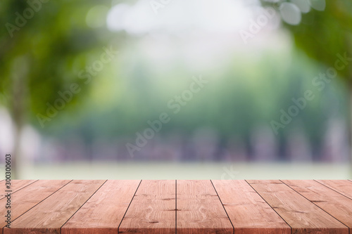 Fotografie, Obraz  Empty wood table top and blurred green tree and lawn in public park background - can used for display or montage your products