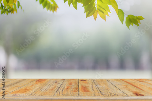 Fototapeta  Empty wood table top and blurred green tree and lawn in public park background - can used for display or montage your products