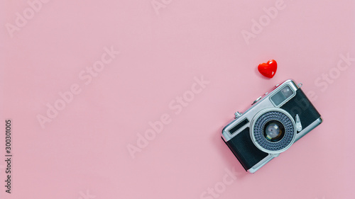 Obraz Top view of vintage old camera and little red heart on pink pastel background with empty space for text.Travel in holiday vacation with retro banner concept. - fototapety do salonu