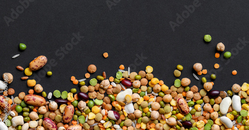 Canvas-taulu Colorful mixed legumes and cereals on black background.