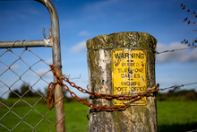 Chain And Gate With Yellow Sign