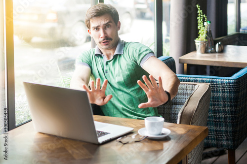 No, stop, please don't touch me! Young scared businessman in green t-shirt sitting with laptop, looking with afraid face and stop sign Wallpaper Mural