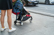 Young mother with her baby stroller with busy city traffic