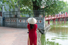 Female Tourist Wearing Vietnamese Traditional Dress Ao Dai With The Huc Bridge At Hoang Kiem Lake On Background