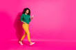 canvas print picture - Full size profile side photo of wavy hair positive cheerful girl use mobile phone go walk on autumn fall holidays chill wear green pullover yellow pants sneakers isolated pink color background