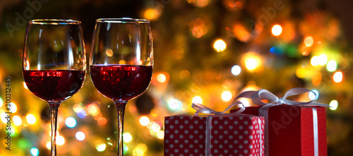 Glasses of wine and Christmas balls on the background of Christmas lights - 300312449