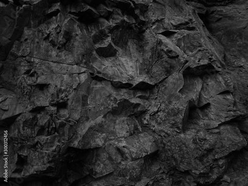 Black abstract grunge backdrop for your design. Dark rock texture. Part of the mountain close-up.