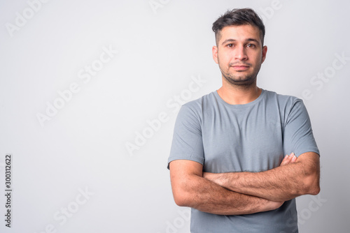 Portrait of young handsome Persian man with arms crossed