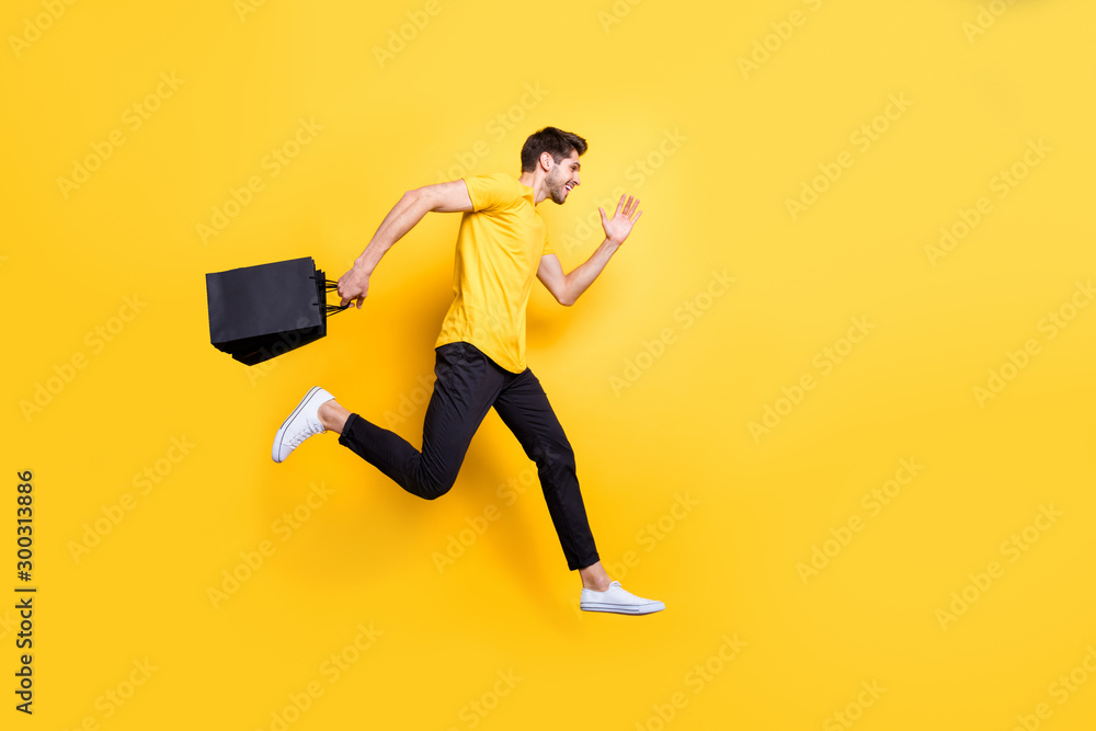 Fototapeta Full size photo of handsome guy jumping high holding packages speed rushing sale shopping wear casual t-shirt pants isolated yellow color background