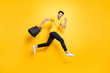 Full size photo of handsome guy jumping high holding many packages speed rushing sale shopping wear casual t-shirt black pants isolated yellow color background