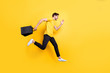 Full size photo of handsome guy jumping high holding packages speed rushing sale shopping wear casual t-shirt pants isolated yellow color background