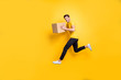 Full size photo of handsome guy jumping high holding parcel box hurry move new apartments transportation wear casual t-shirt pants isolated yellow color background