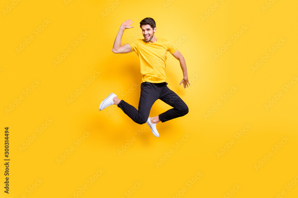Fototapeta Hi there guys. Full body photo of handsome guy jumping high waving arm see old friends on streets wear casual t-shirt black trousers isolated yellow color background