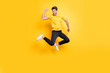 Hi there guys. Full body photo of handsome guy jumping high waving arm see old friends on streets wear casual t-shirt black trousers isolated yellow color background