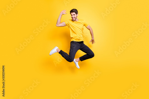 Poster Ecole de Danse Hi there guys. Full body photo of handsome guy jumping high waving arm see old friends on streets wear casual t-shirt black trousers isolated yellow color background