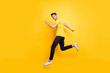 Full length body size view of his he nice attractive sportive cheerful cheery guy running marathon isolated over bright vivid shine vibrant yellow color background
