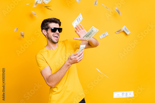 Fototapeta Photo of young handsome careless guy throwing money banknotes away wealthy person wear sun specs casual t-shirt isolated bright yellow color background obraz