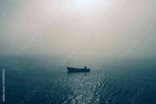 Stampa su Tela Fishing boat and fisherman in the sea, foggy morning over the water