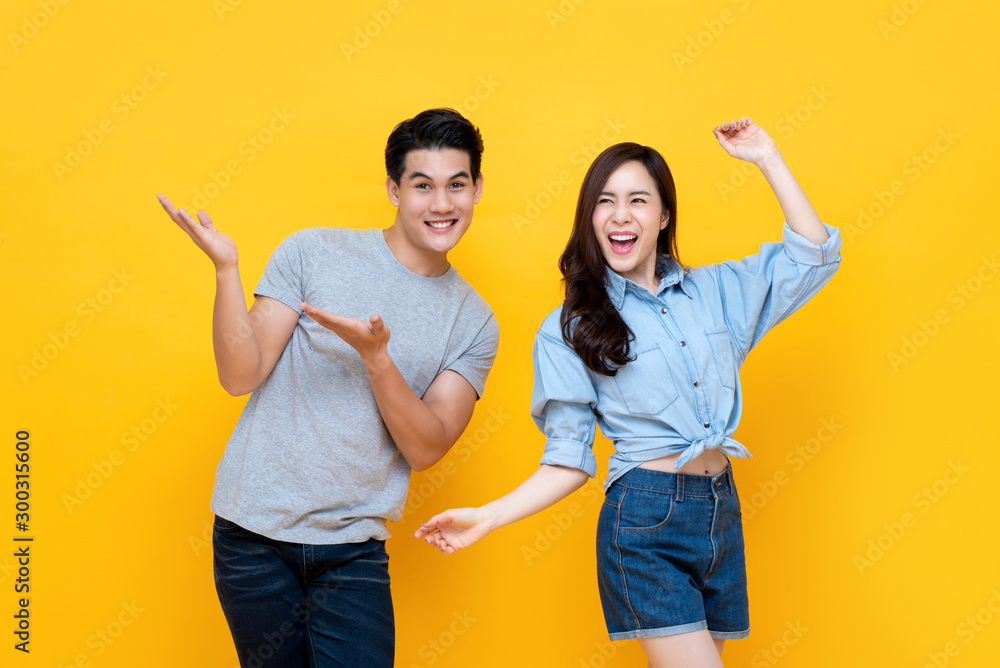 Fototapety, obrazy: Cheerful excited young Asian man and woman smiling and dancing