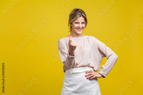 Photo  Come here! Portrait of playful happy young woman with fair hair in casual beige blouse standing, calling with finger gesture, inviting to come in