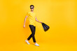 Full body photo of handsome guy carry boutique bags make abroad shopping go fashionable mall wear casual t-shirt black pants isolated yellow color background