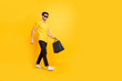 Full length body size view of his he nice attractive fashionable trendy cheerful cheery guy carrying bags new clothing things strolling isolated over bright vivid shine vibrant yellow color background
