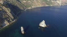 Aerial Video Of Fiolent Cape In Crimea, Sevastopol. Amazing Place, Beauty Nature. Panoramic Video Of Protruding Rocks From Sea, Yacht Staying At Anchor Light Cloudy Sky Background.