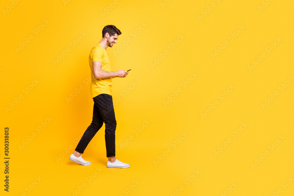 Fototapeta Full length body size photo of cheerful attractive man with bristle smiling toothily focused on reading feednews on his phone wearing yellow t-shirt white footwear isolated bright color background