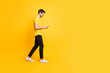 Full length body size photo of cheerful attractive man with bristle smiling toothily focused on reading feednews on his phone wearing yellow t-shirt white footwear isolated bright color background