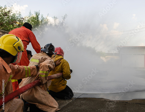 Canvas Prints Fishing Firefighters are practicing fire fighting prevent emergencies. Use large water hose to put out the fire. The fire caused enormous losses. Must do training prevent fires that may occur in the future.