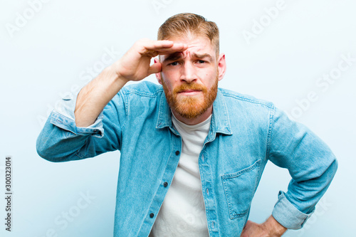 Photo young red head man looking bewildered and astonished, with hand over forehead lo