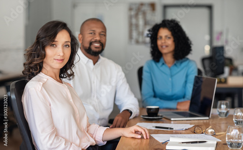 Fotografía  Confident diverse businesspeople sitting together at an office table