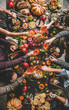 Family celebrating Thanksgiving day. Flat-lay of feasting peoples hands clinking glasses with champagne over Friendsgiving table with Autumn food, roasted turkey and pumpkin pie over wooden table