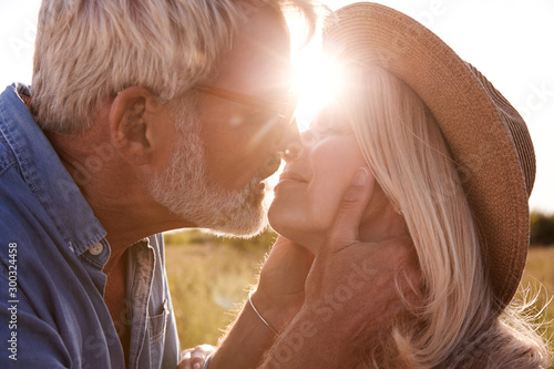 Obraz na plátně  Loving Mature Couple In Countryside About To Kiss Against Flaring Sun