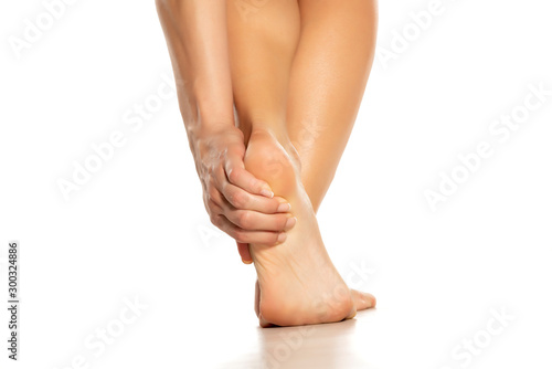 woman holding her painful heel on white background Obraz na płótnie