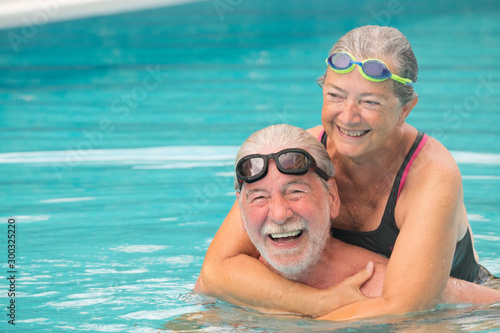 Fotomural  couple of two seniors hugged in the water of swimming pool - active man and woma