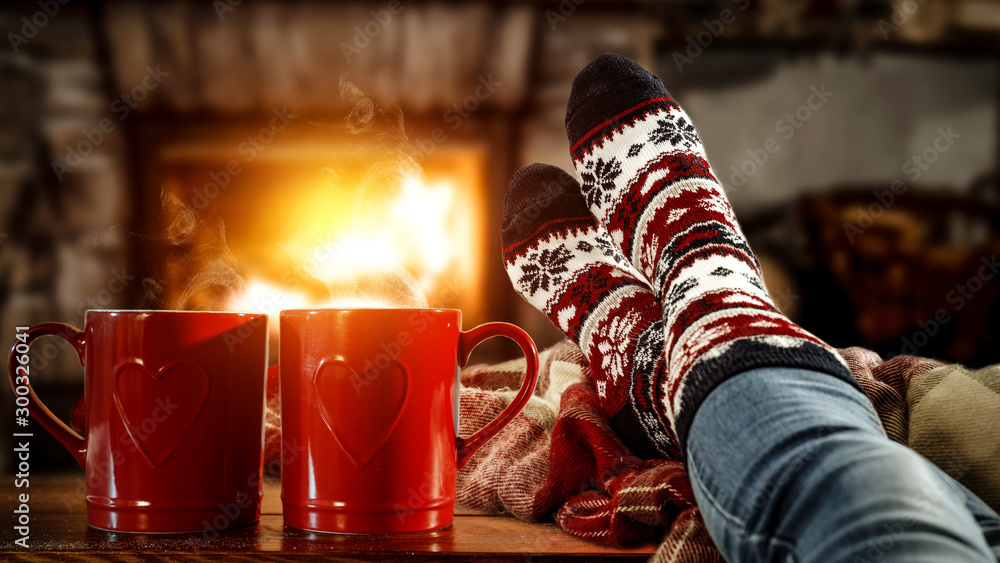 Fototapety, obrazy: Woman legs with christmas socks and fireplace in home interior.