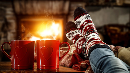 Woman legs with christmas socks and fireplace in home interior.
