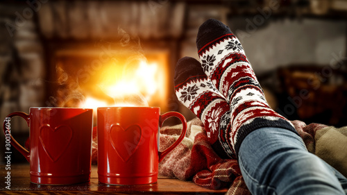 Foto auf Leinwand Tee Woman legs with christmas socks and fireplace in home interior.