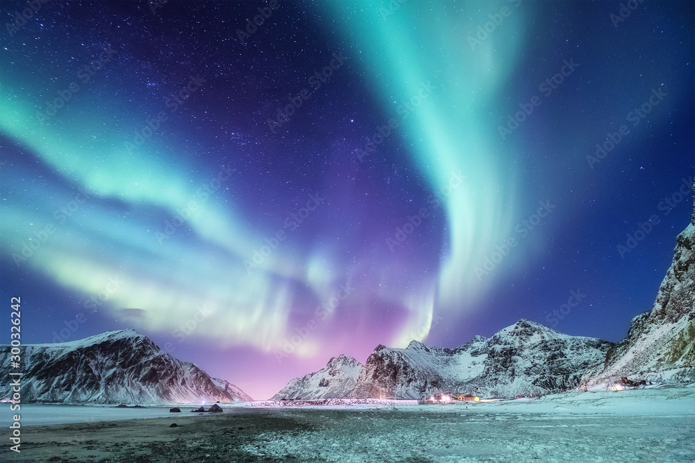 Fototapeta Aurora borealis on the Lofoten islands, Norway. Green northern lights above mountains. Night winter landscape with aurora. Natural background in the Norway