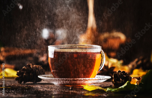 Tuinposter Thee Autumn hot black tea in glass cup, old wooden table background, selective focus