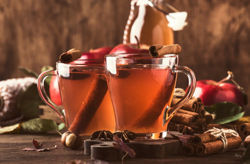 Hot mulled apple cider vinegar with cinnamon sticks, cloves and anise on wooden background. Traditional autumn, winter drinks and cocktails