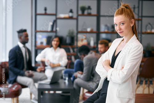 Young caucasian businesswoman with auburn hair wearing white blazer stand confid Wallpaper Mural