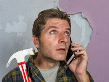 Funny Portrait Of Messy And Frustrated Man Calling Domestic Insurance On Mobile Phone For Repair Mess He Did With A Hammer Cracking The Wall Needing Professional Help