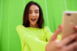 canvas print picture - Amazed young woman holds in hands the smart phone to taking self portrait. Teenage girl has surprised expression during conversation online with her friends, posing against green outdoor background